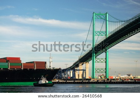 A tug boat assists a large container ship as it passes beneath the Vincent Thomas bridge in the port of Los Angeles. - stock photo
