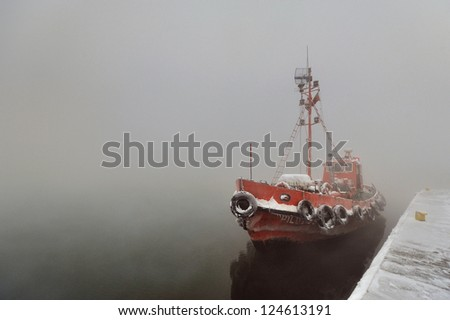 A tug boat motors down a river on a cold and foggy winter day - stock photo