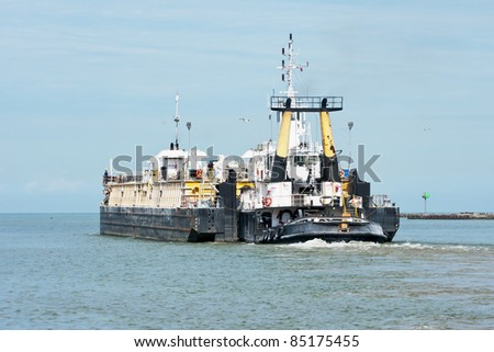 A tug boat pushes a cement barge out of the Cuyahoga River and into Lake Erie at Cleveland, Ohio - stock photo