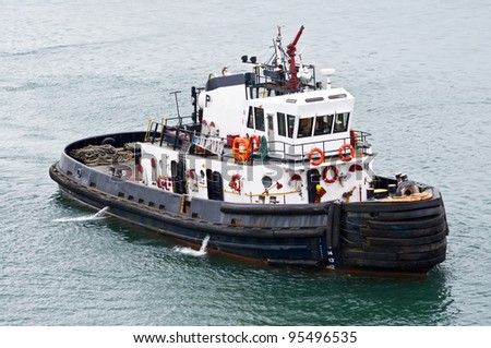 A tug boat stands ready to help ships in the Panama Canal - stock photo