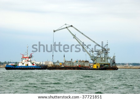 A tug boat towing a sea crane into the port