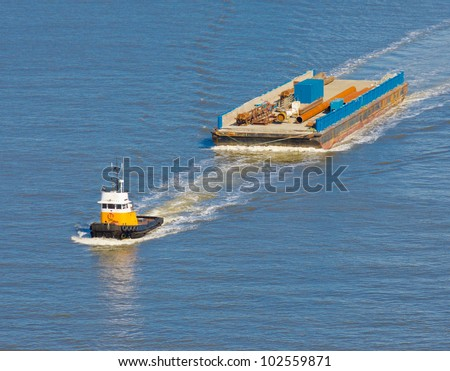 A tug boat towing barge. - stock photo