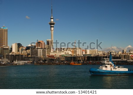a tug is sailling through Auckland Harbour - stock photo