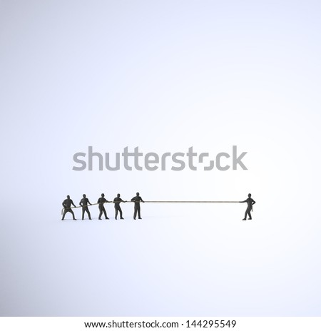 A tug of war between a group of people and a single man - stock photo