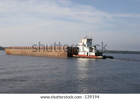 A tug transporting empty coal barges to be refilled