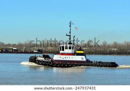 A Tugboat cruising down the Mississippi River at New Orleans. - stock photo