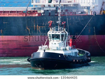 A tugboat dwarfed by the large ship it is pushing - stock photo