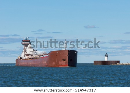 A tugboat pushing a massive barge laden with taconite pellets passes a navigation beacon as it enters the harbor at the Port of Cleveland, Ohio on Lake Erie