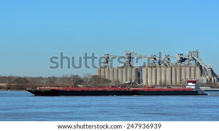 A tugboat pushing barges past grain storage silos on the Mississippi River at New Orleans. - stock photo