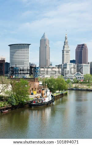 A tugboat sits moored along the bank of the Cuyahoga River with the downtown area of Cleveland, Ohio in the distance - stock photo