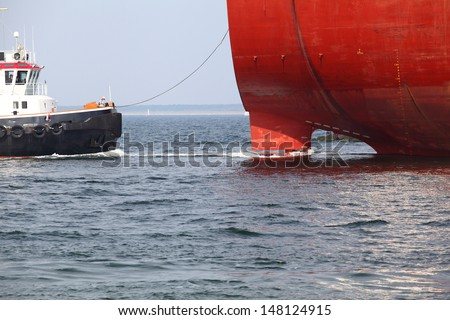 A tugboat takes a cargo vessel on the leash/Docking Maneuver - stock photo