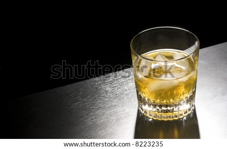 a tumbler of whiskey with ice against black - stock photo