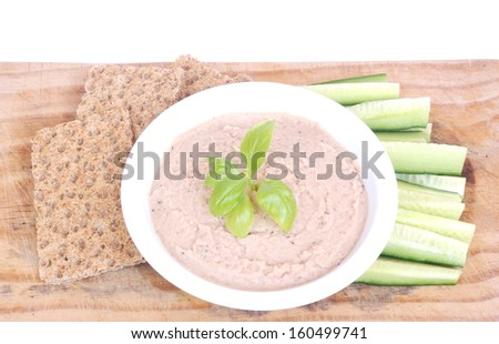 A tuna fish dip garnished with basil leaves in a bowl surrounded  by English cucumber sticks and crisp bread on a wooden board. Image isolated on white studio background.