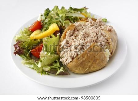 A Tuna Mayonnaise baked potato on a plate with side salad - stock photo