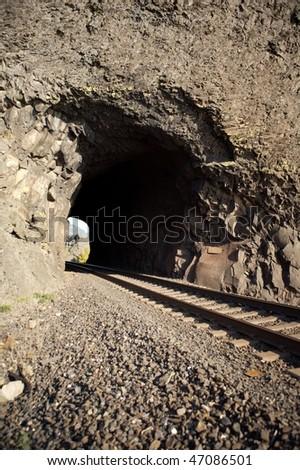 A tunnel cutting through a mountain - stock photo