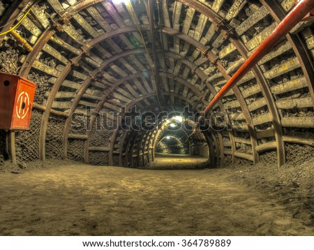 A tunnel in a coal mine leading deep  into the earth - stock photo
