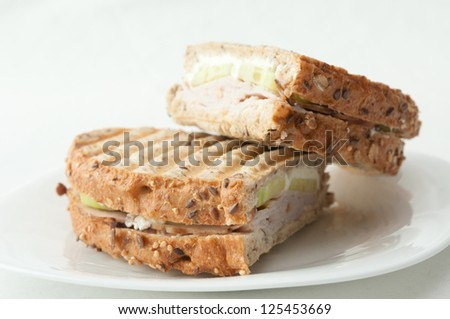 a turkey and cucumber sandwich grilled in a panini press - stock photo