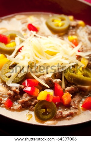 "A turkey based ""white chili"" topped with cheese and peppers"
