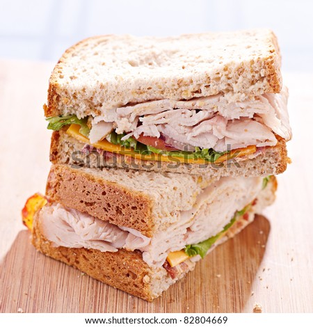 a turkey club sandwich cut in halves with selective focus - stock photo