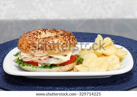 A turkey, swiss cheese, tomato and lettuce sandwich on an onion bagel with a side of chips.
