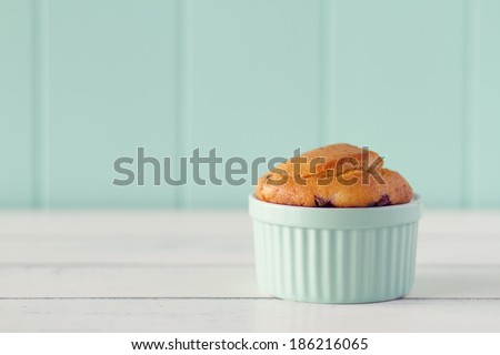 A turquoise classic white ware baking bowl with a muffins on a white wooden table with a robin egg blue background. Vintage look. - stock photo