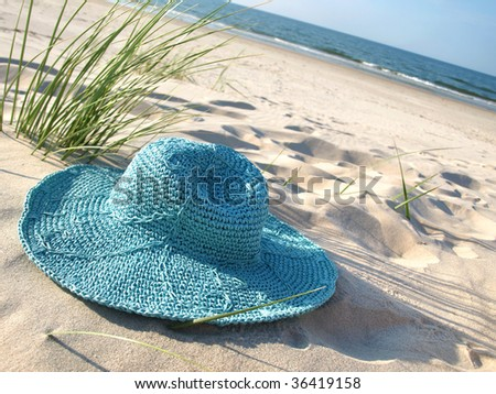 A turquoise straw hat on the sand  of baltic beach.
