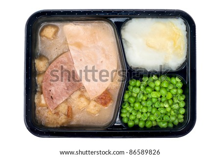 A TV dinner consisting of turkey, ham, peas and mashed potatoes isolated on white - stock photo