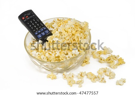 A TV or DVD remote control in a full glass bowl of fresh buttered popcorn