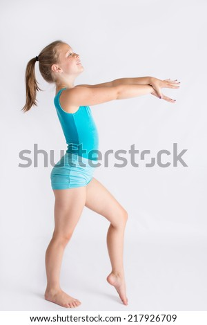 A tween girl standing in profile, smiling, and posing in a gymnastics stance. - stock photo