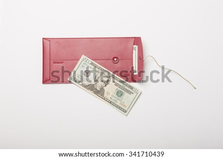 A twenty dollars and a red leather envelope top view isolated white at the studio.