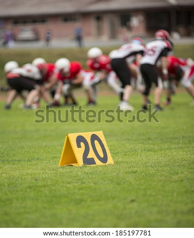 A twenty yard sign in front and a group of american footballers in the back.
