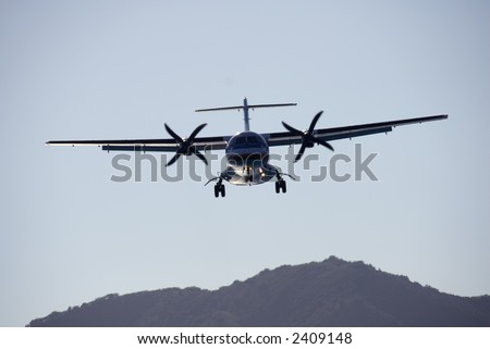 A twin-engined turboprop passenger plane landing at dusk. - stock photo