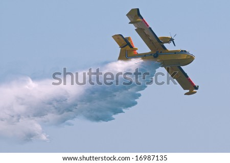 A twin-engined water bomber dumping its load on a forest fire. - stock photo