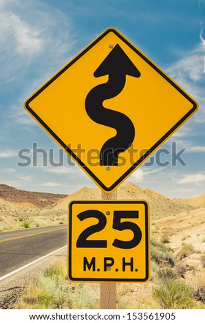 A Twisty Road Sign with Speed Limit - stock photo