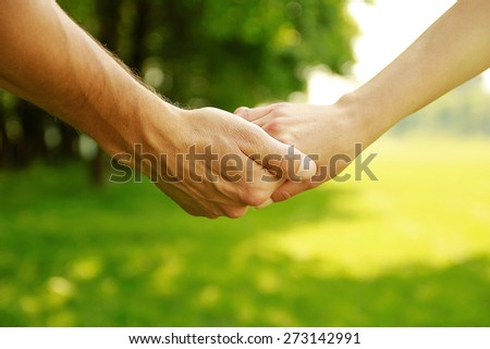 a two hands in love couple on nature - stock photo