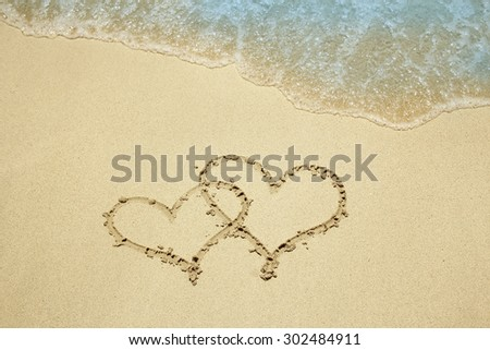 a two hearts in the sand on the beach - stock photo