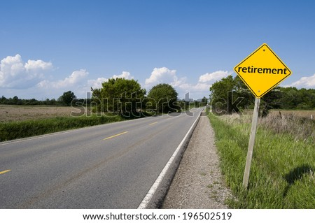 A two lane road with a sign on the side of the road that says retirement. - stock photo