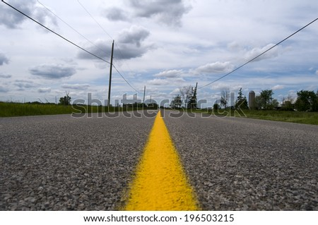 A two lane road with a yellow stripe down the middle.