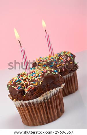A two tasty muffin chocolate with candle isolated on color background. Flame at focus and shallow depth of field