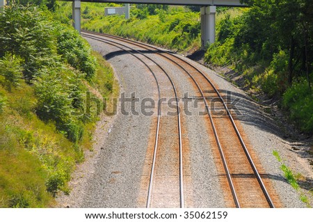A two-track railroad curves under a bridge amid greenery - stock photo