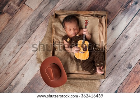 A two week old baby boy wearing crocheted overalls and playing a tiny acoustic guitar. He is lying in a wooden crate lined with burlap. Shot in the studio on a rustic, wood background. - stock photo