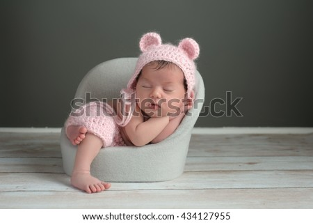 A two week old newborn baby girl sleeping in a little chair. She is wearing a crocheted, pink bear bonnet and matching shorts. Shot in the studio on a gray background. - stock photo