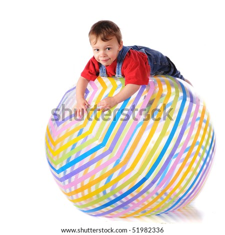 A two-year-old balanced over the top of a giant beach ball.  Isolated on white. - stock photo