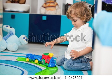 A two year old child playing in his room with a toy train - stock photo
