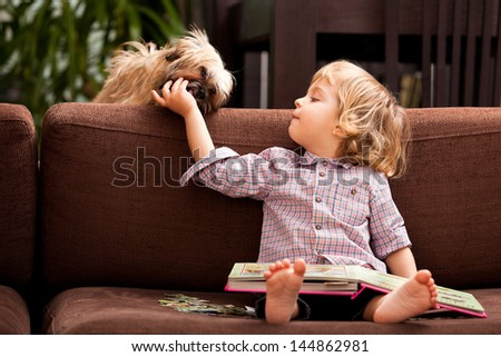 A two year old child sitting on the sofa with a book in his lap feeding his little dog