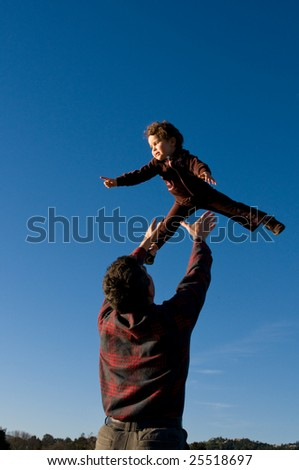 A two year old girl is pointing at something while being tossed up by her father.