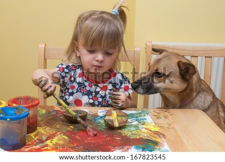 A two year old girl painting at the table with the family dog sitting beside her.