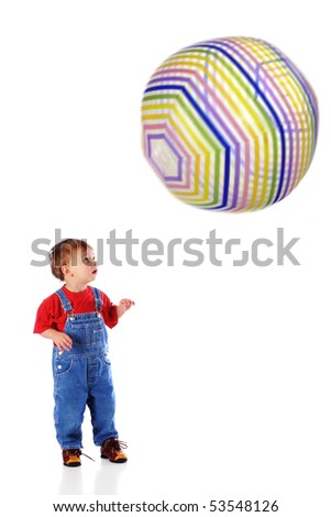 A two-year-old mezmerized by the giant beach ball coming towards him.  The ball has motion blur.  Isolated on white. - stock photo