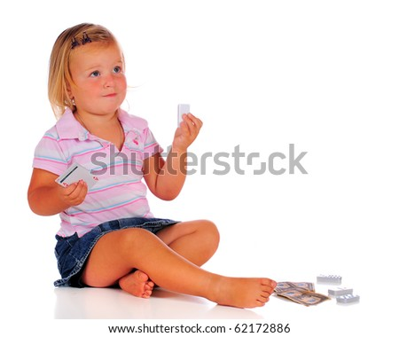 A two-year-old playing with game pieces: cards, tiles and money.  Isolated on white. - stock photo