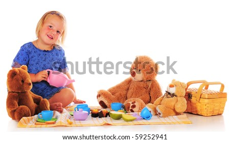 A two year-old ready to pour tea for her teddy bears.  Isolated on white. - stock photo